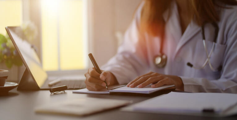 close-up-view-young-female-doctor-writing-medical-charts-with-tablet-office-room
